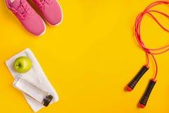 Le ` s d'athlète a placé avec l'habillement femelle, la corde à sauter et la bouteille de l'eau sur le fond jaune Photographie stock libre de droits