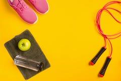 Le ` s d'athlète a placé avec l'habillement femelle, la corde à sauter et la bouteille de l'eau sur le fond jaune Photo libre de droits
