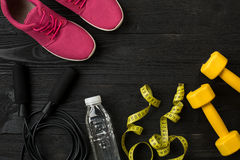 Le ` s d'athlète a placé avec l'habillement, les espadrilles et la bouteille femelles de l'eau sur le fond foncé Images libres de droits