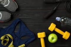 Le ` s d'athlète a placé avec l'habillement, les espadrilles et la bouteille femelles de l'eau sur le fond foncé Photo stock