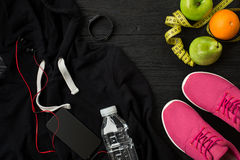 Le ` s d'athlète a placé avec l'habillement, les espadrilles et la bouteille femelles de l'eau sur le fond foncé Photo libre de droits