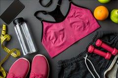 Le ` s d'athlète a placé avec l'habillement, les espadrilles et la bouteille femelles de l'eau sur le fond gris Photo libre de droits