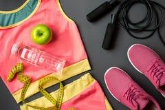 Le ` s d'athlète a placé avec l'habillement, les espadrilles et la bouteille femelles de l'eau sur le fond gris Images stock