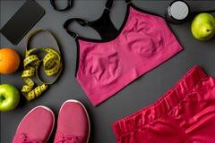 Le ` s d'athlète a placé avec l'habillement, les espadrilles et la bouteille femelles de l'eau sur le fond gris Image stock