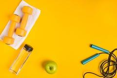 Le ` s d'athlète a placé avec l'habillement, les haltères et la bouteille femelles de l'eau sur le fond jaune Image stock