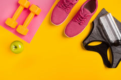 Le ` s d'athlète a placé avec l'habillement, les haltères et la bouteille femelles de l'eau sur le fond jaune Photos libres de droits