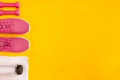 Le ` s d'athlète a placé avec l'habillement, les haltères et la bouteille femelles de l'eau sur le fond jaune Photographie stock