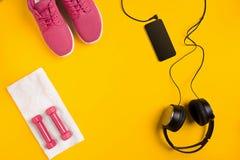 Le ` s d'athlète a placé avec l'habillement, les haltères et la bouteille femelles de l'eau sur le fond jaune Image libre de droits