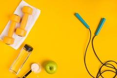 Le ` s d'athlète a placé avec l'habillement, les haltères et la bouteille femelles de l'eau sur le fond jaune Images stock