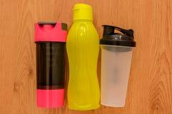 Le ` s d'athlète a placé avec trois bouteilles de l'eau, dans une rangée sur le fond en bois Image stock
