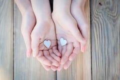 Le ` s d'enfant et de mère remet tenir le coeur Images stock