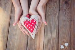 Le ` s d'enfant et de mère remet tenir le coeur Photos stock