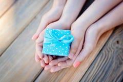 Le ` s d'enfant et de mère remet tenir un cadeau Photos stock