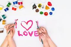 Le ` s d'enfant remet peindre un coeur Images stock