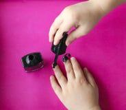 Le ` s d'enfants remet à peinture leurs ongles avec le vernis à ongles noir manucure du ` s d'enfants manucure noire sur les ongl image stock