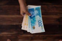 Le ` s d'enfants remet compter des comptes dans le shelley 200 le shekel et 100 Image libre de droits