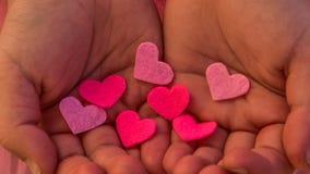 Le ` s d'enfants remet tenir le coeur sur un fond rose Concept de l'amour, soin, foi, espoir, pureté Images stock