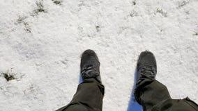 Le ` s d'hommes d'espadrilles frappent du pied sur la neige Photographie stock