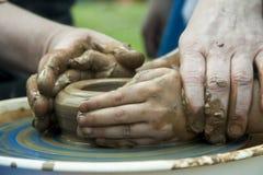 Le ` s d'hommes et les mains du ` s d'enfants sur un ` s de potier roulent Photos stock