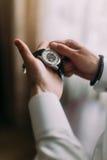 Le ` s d'hommes remet se tenir et s'enrouler vers le haut de la montre mécanique photo stock