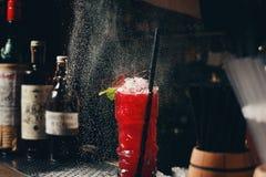 Le ` s de barman remet arroser le jus dans le verre de cocktail rempli de boisson alcoolisée sur le fond foncé Image libre de droits
