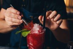 Le ` s de barman remet arroser le jus dans le verre de cocktail rempli de boisson alcoolisée sur le fond foncé Photographie stock