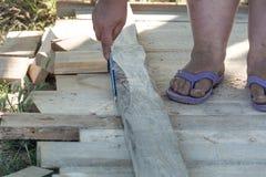 Le ` s de charpentier remet mesurer une image de plan rapproché de conseil en bois photos stock