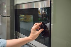 Le ` s de femme remet ajuster le bouton de synchronisation sur la micro-onde photo libre de droits
