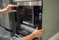 Le ` s de femme remet le bouton de pressing à la porte ouverte de micro-onde photos stock