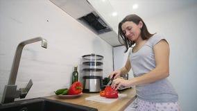 Le ` s de femme remet couper en tranches le paprika rouge doux sur une planche à découper en bois Concept sain de nourriture Mouv banque de vidéos