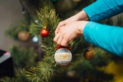 Le ` s de femme remet décorer l'arbre de Noël avec la boule Image stock