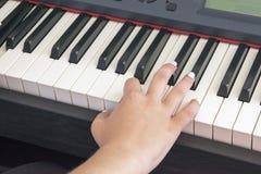 Le ` s de femme remet jouer sur le piano électrique images stock