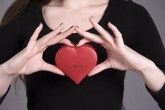Le ` s de femme remet juger une boîte de forme de coeur avec l'amour de mot imprimée Images libres de droits