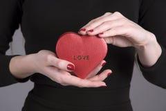Le ` s de femme remet juger une boîte de forme de coeur avec l'amour de mot imprimée Photos libres de droits