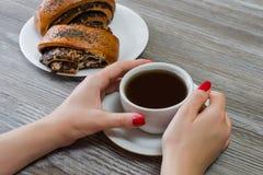 Le ` s de femme remet la tasse émouvante de thé, petits pains avec des clous de girofle sur photos libres de droits