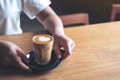Le ` s de femme remet tenir et donner un verre de café chaud avec l'art de latte de coeur sur la table en bois de vintage Photos stock