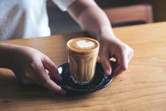 Le ` s de femme remet tenir et donner un verre de café chaud avec l'art de latte de coeur sur la table en bois de vintage Images libres de droits