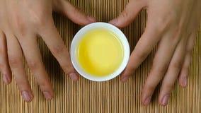 Le ` s de femme remet tenir la tasse blanche de fond en bambou de thé chinois, vue supérieure Une femme tenant une tasse de thé J Photos stock