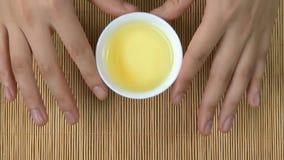 Le ` s de femme remet tenir la tasse blanche de fond en bambou de thé chinois, vue supérieure Une femme tenant une tasse de thé J Photos libres de droits