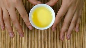 Le ` s de femme remet tenir la tasse blanche de fond en bambou de thé chinois, vue supérieure Une femme tenant une tasse de thé J Photographie stock libre de droits