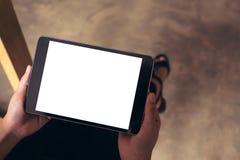 Le ` s de femme remet tenir le PC noir de comprimé avec l'écran de bureau blanc vide image stock