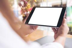 Le ` s de femme remet tenir le PC noir de comprimé avec la tasse de bureau blanche vide d'écran, d'ordinateur portable et de café images libres de droits