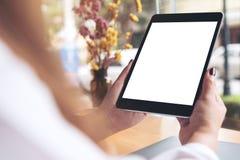 Le ` s de femme remet tenir le PC noir de comprimé avec la tasse de bureau blanche vide d'écran, d'ordinateur portable et de café photos libres de droits