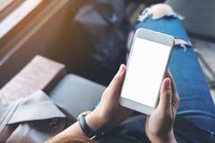 Le ` s de femme remet tenir le téléphone portable blanc avec l'écran noir vide sur la cuisse avec le fond en bois de plancher en  photos stock
