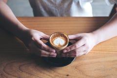 Le ` s de femme remet tenir un verre de café chaud avec l'art de latte de coeur sur la table en bois de vintage Photos stock