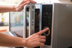 Le ` s de femme soumet la micro-onde fermante Oven Door And Preparing Food image stock
