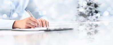 Le ` s de femme de thème de Noël remet l'écriture sur la feuille de papier dans un cli photographie stock libre de droits
