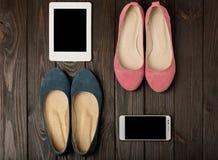 Le ` s de femmes chausse des ballerines rose, bleu et beige sur une obscurité en bois Image libre de droits