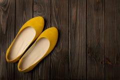 Le ` s de femmes jaunes chausse des ballerines sur le fond en bois Photo stock