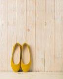 Le ` s de femmes jaunes chausse des ballerines sur le fond en bois Photographie stock